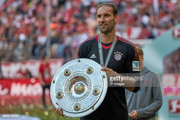 Goalkeeper Tom Starke of Bayern Muenchen poses with the Championship trophy in celebration of the 67th German Championship title following he...