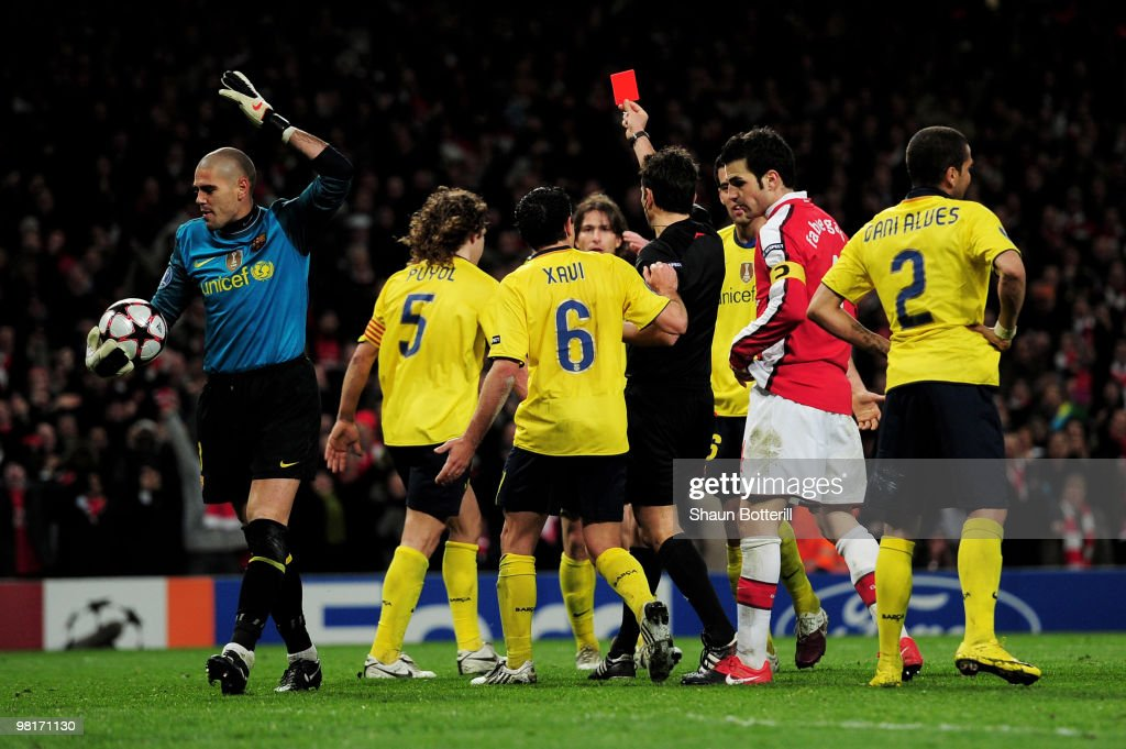 Goalkeeper Victor Valdes (L) of Barcelona reacts as team mate Carles Puyol #5 is shown a red card by referee Massimo Busacca of Switerland after bringing down Cesc Fabregas (2nd R) of Arsenal for a penalty during the UEFA Champions League quarter final first leg match between Arsenal and FC Barcelona at the Emirates Stadium on March 31, 2010 in London, England.