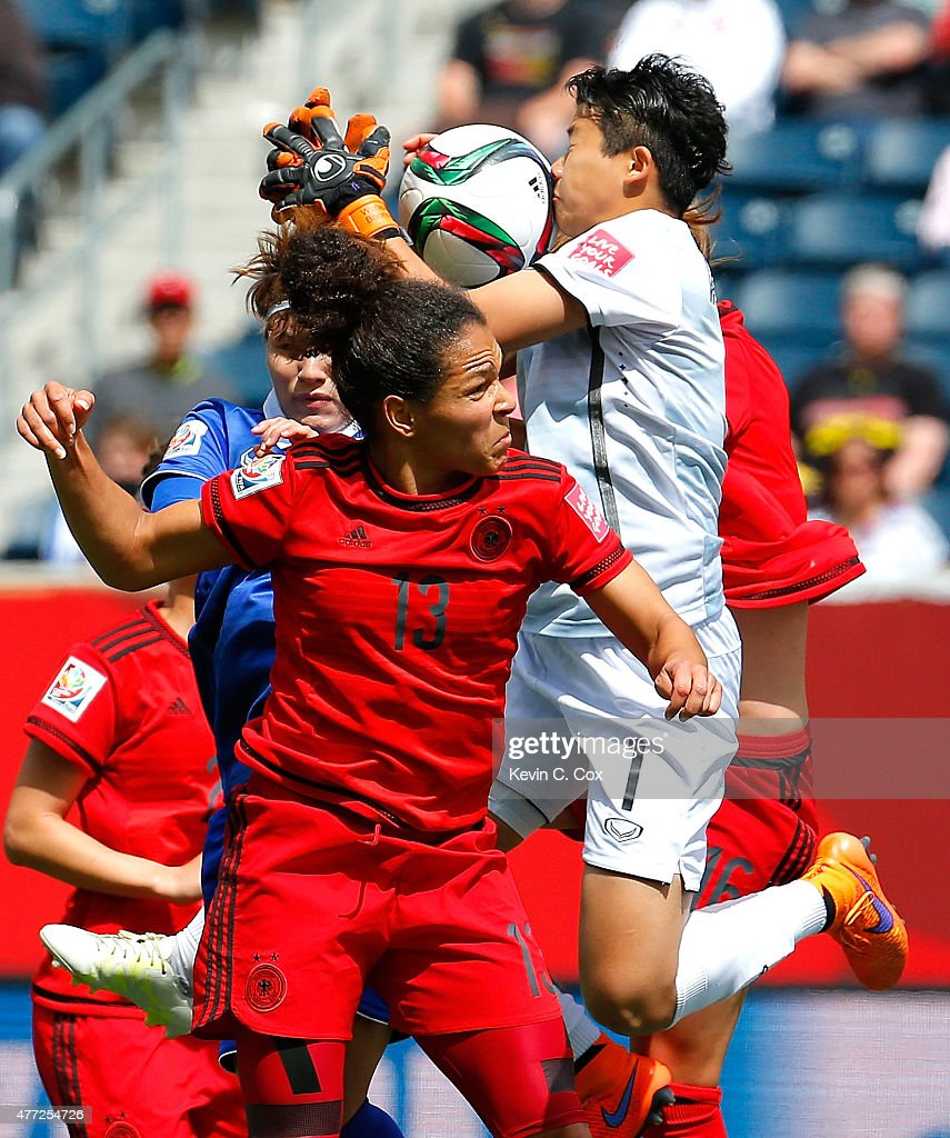 Goalkeeper Waraporn Boonsing #1 of Thailand saves a shot on goal against Celia Sasic #13 and Melanie Leupolz #16 of Germany during the FIFA Women's World Cup Canada 2015 match between Thailand and Germany at Winnipeg Stadium on June 15, 2015 in Winnipeg, Canada.