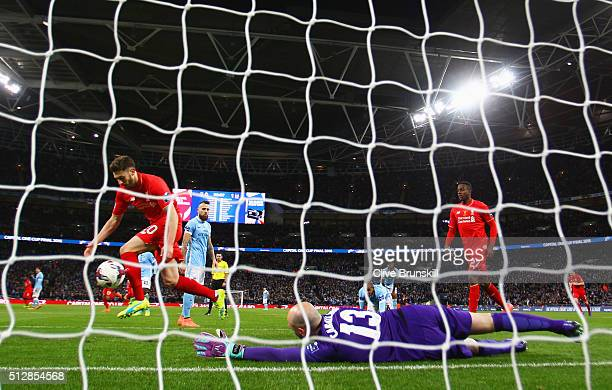 Goalkeeper Willy Caballero of Manchester City reacts as Adam Lallana of Liverpool celebrates their equalising goal by Philippe Coutinho during the...