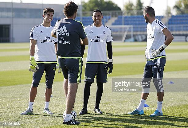 Goalkeepers coach Xavi Valero of Real Madrid talks to his players Ruben Yanez Keylor Navas and Kiko Casillas during a training session at Valdebebas...