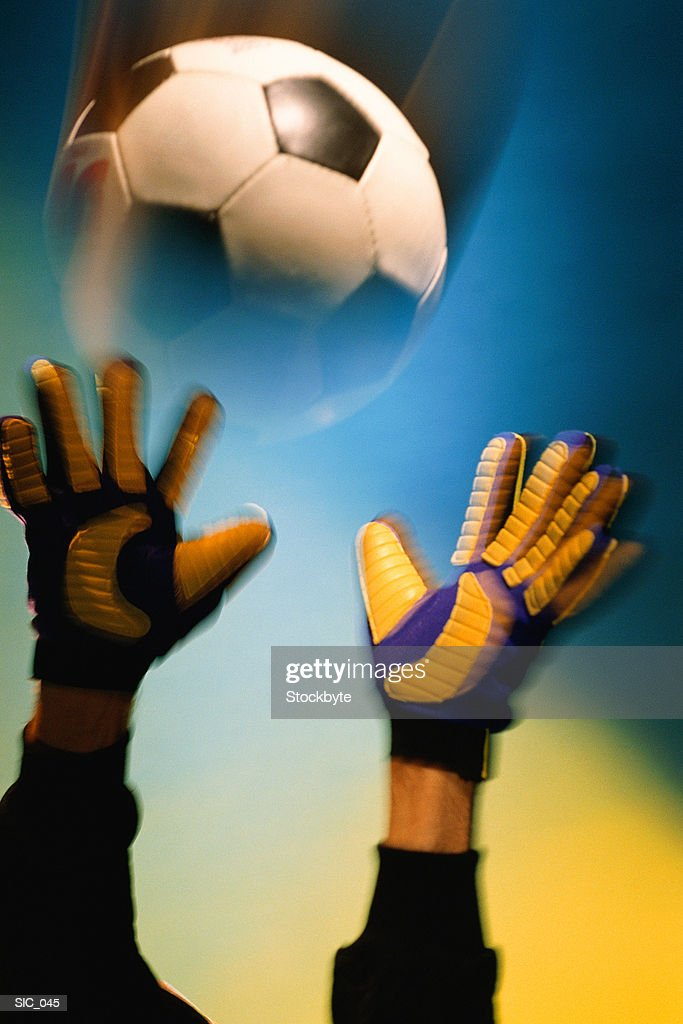 Goalkeeper's hands reaching out to soccer ball