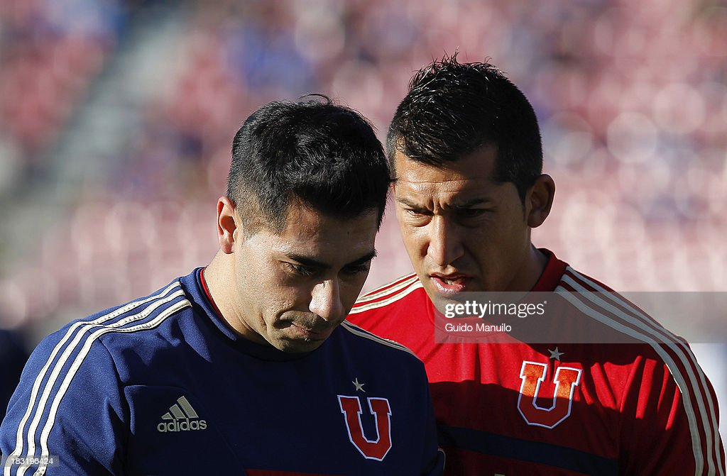 Goalkeepers of U de Chile Jonnhy Herrera and <a gi-track='captionPersonalityLinkClicked' href=/galleries/search?phrase=Luis+Marin&family=editorial&specificpeople=555151 ng-click='$event.stopPropagation()'>Luis Marin</a> warm up during a match between O'Higgins and U de Chile as part of the Torneo Apertura at National Stadium, on October 05, 2013 in Santiago, Chile.