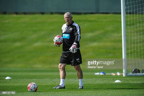 Goalkeeping Coach Simon Smith holds a ball and walks on the pitch during a Newcastle United Training session at The Newcastle United Training Centre...