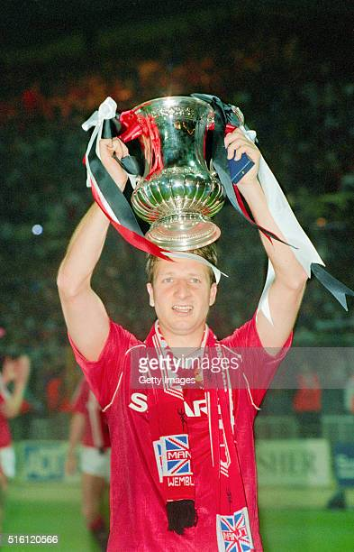 Goalscorer Lee Martin of Manchester United holds the trophy aloft after their victory in the FA Cup final replay against Crystal Palace at Wembley...