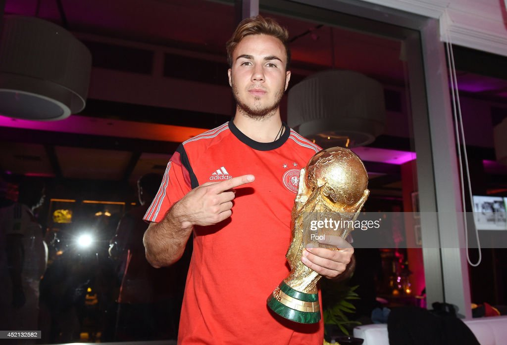 Goalscorer Mario Gotze of Germany poses with the World Cup trophy as he celebrates with teammates at a party, after winning the 2014 FIFA World Cup Brazil Final match against Argentina, at Sheraton Hotel on July 13, 2014 in Rio de Janeiro, Brazil.