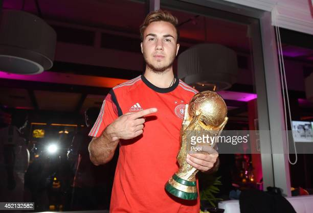 Goalscorer Mario Gotze of Germany poses with the World Cup trophy as he celebrates with teammates at a party after winning the 2014 FIFA World Cup...