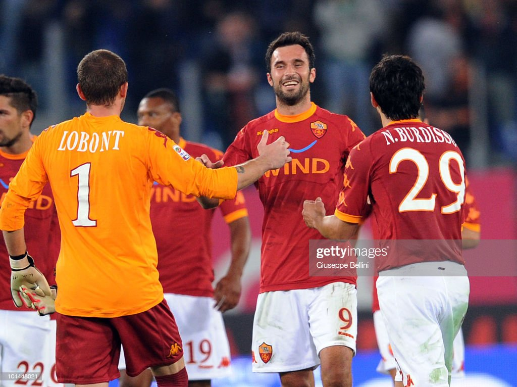 Goalscorer Mirko Vucinic of Roma celebrates his team's 10 victory with teammates Bogdan Lobont and Nicolas Burdisso after the Serie A match between...