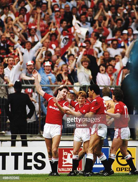 Goalscorer Norman Whiteside is congratulated by team mates Gordon Strachan Paul McGrath and Mike Duxbury after scoring the winning goal during the...