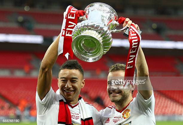 Goalscorers Jesse Lingard and Juan Mata of Manchester United celebrate with the trophy after winning The Emirates FA Cup Final match between...