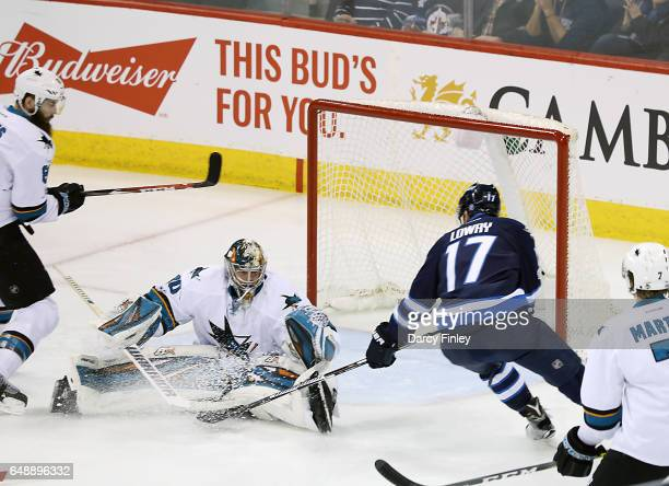 Goaltender Aaron Dell of the San Jose Sharks sprawls at the top of the crease as he stops a shot by Adam Lowry of the Winnipeg Jets during second...