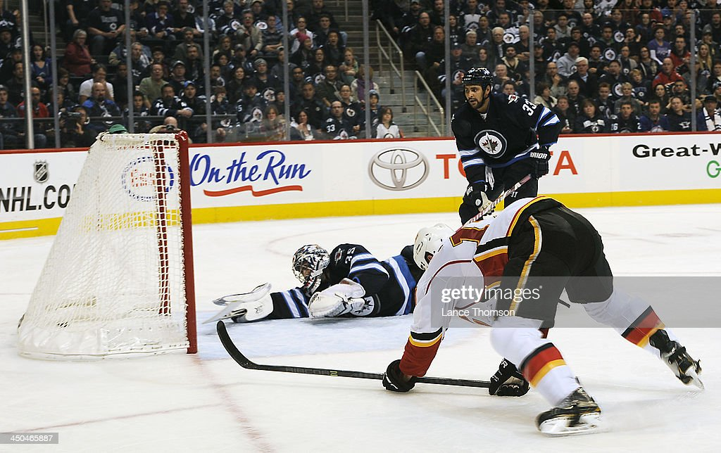 Goaltender <a gi-track='captionPersonalityLinkClicked' href=/galleries/search?phrase=Al+Montoya&family=editorial&specificpeople=213916 ng-click='$event.stopPropagation()'>Al Montoya</a> #35 and <a gi-track='captionPersonalityLinkClicked' href=/galleries/search?phrase=Dustin+Byfuglien&family=editorial&specificpeople=672505 ng-click='$event.stopPropagation()'>Dustin Byfuglien</a> #33 of the Winnipeg Jets look at the puck in the net after <a gi-track='captionPersonalityLinkClicked' href=/galleries/search?phrase=Lance+Bouma&family=editorial&specificpeople=4303790 ng-click='$event.stopPropagation()'>Lance Bouma</a> #17 of the Calgary Flames scored a goal during third period action at the MTS Centre on November 18, 2013 in Winnipeg, Manitoba, Canada.