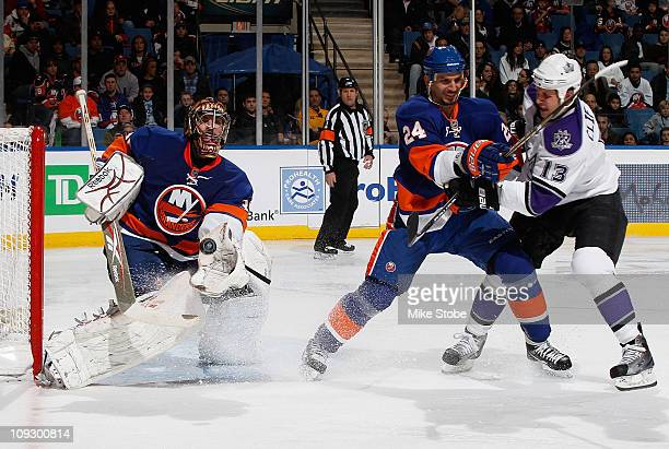 Goaltender Al Montoya of the New York Islanders makes the save as teammate Radek Martinek and Kyle Clifford of the Los Angeles Kings battle in front...