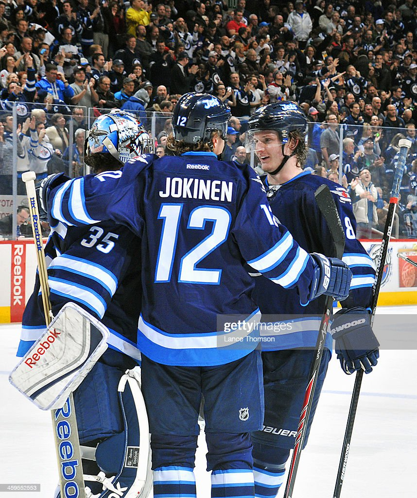 Goaltender <a gi-track='captionPersonalityLinkClicked' href=/galleries/search?phrase=Al+Montoya&family=editorial&specificpeople=213916 ng-click='$event.stopPropagation()'>Al Montoya</a> #35 of the Winnipeg Jets gets congratulated by teammates <a gi-track='captionPersonalityLinkClicked' href=/galleries/search?phrase=Olli+Jokinen&family=editorial&specificpeople=202946 ng-click='$event.stopPropagation()'>Olli Jokinen</a> #12 and <a gi-track='captionPersonalityLinkClicked' href=/galleries/search?phrase=Jacob+Trouba&family=editorial&specificpeople=8050718 ng-click='$event.stopPropagation()'>Jacob Trouba</a> #8 after backstopping the Jets to a 6-4 victory over the Minnesota Wild at the MTS Centre on December 27, 2013 in Winnipeg, Manitoba, Canada.
