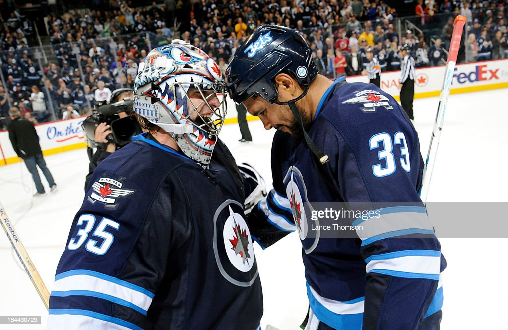 Goaltender <a gi-track='captionPersonalityLinkClicked' href=/galleries/search?phrase=Al+Montoya&family=editorial&specificpeople=213916 ng-click='$event.stopPropagation()'>Al Montoya</a> #35 of the Winnipeg Jets is all smiles as he celebrates with teammate <a gi-track='captionPersonalityLinkClicked' href=/galleries/search?phrase=Dustin+Byfuglien&family=editorial&specificpeople=672505 ng-click='$event.stopPropagation()'>Dustin Byfuglien</a> #33 after backstopping the Jets to a 3-0 victory over the New Jersey Devils at the MTS Centre on October 13, 2013 in Winnipeg, Manitoba, Canada.