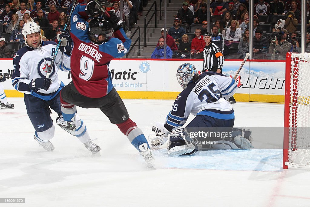 Goaltender <a gi-track='captionPersonalityLinkClicked' href=/galleries/search?phrase=Al+Montoya&family=editorial&specificpeople=213916 ng-click='$event.stopPropagation()'>Al Montoya</a> #35 of the Winnipeg Jets makes a save as his teammate Mark Stuart #5 knocks <a gi-track='captionPersonalityLinkClicked' href=/galleries/search?phrase=Matt+Duchene&family=editorial&specificpeople=4819304 ng-click='$event.stopPropagation()'>Matt Duchene</a> #9 of the Colorado Avalanche off-balance at the Pepsi Center on October 27, 2013 in Denver, Colorado.