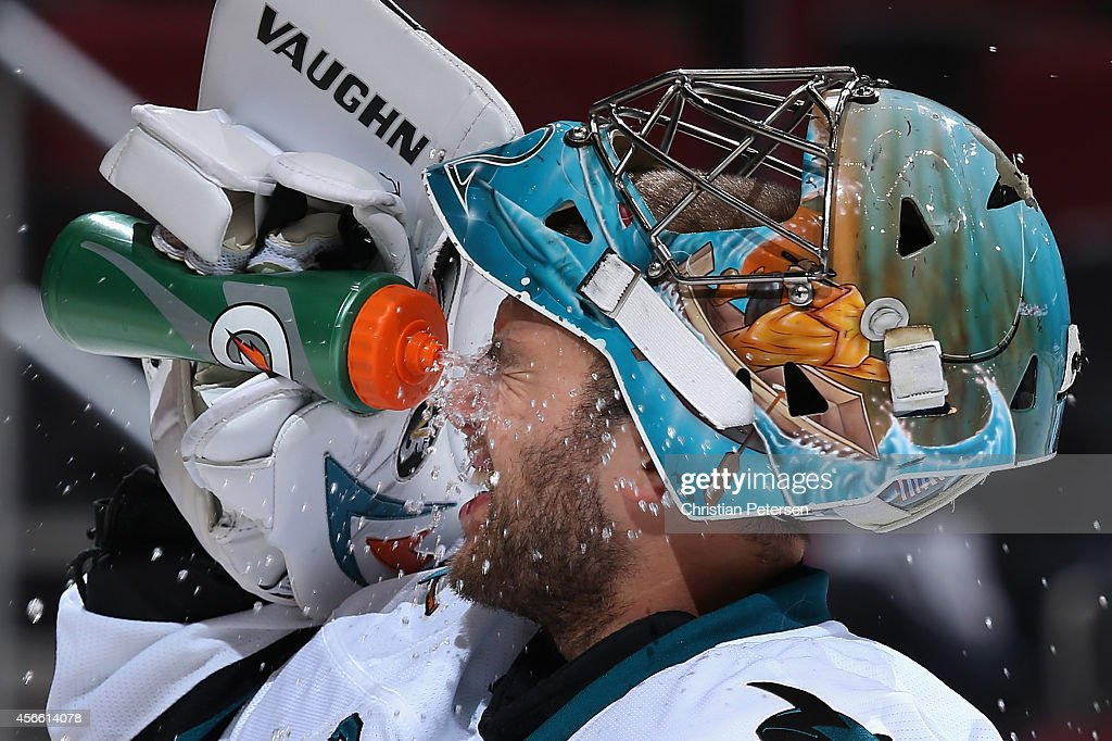 Goaltender Alex Stalock of the San Jose Sharks sprays water in the his face during a break from the preseason NHL game against the Arizona Coyotes at...