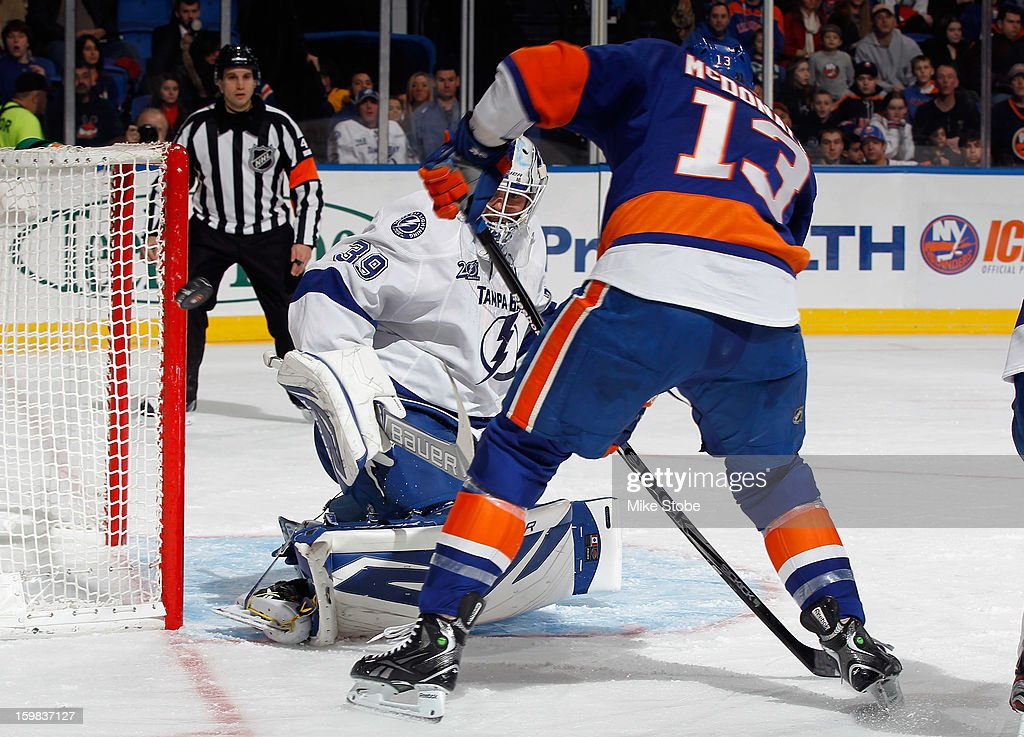 Goaltender Anders Lindback #39 of the Tampa Bay Lightning defends the net as Colin McDonald #13 of the New York Islanders looks for the rebound at Nassau Veterans Memorial Coliseum on January 21, 2013 in Uniondale, New York.