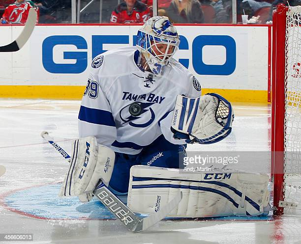 Goaltender Anders Lindback of the Tampa Bay Lightning makes a chest save during the game against the New Jersey Devils at the Prudential Center on...