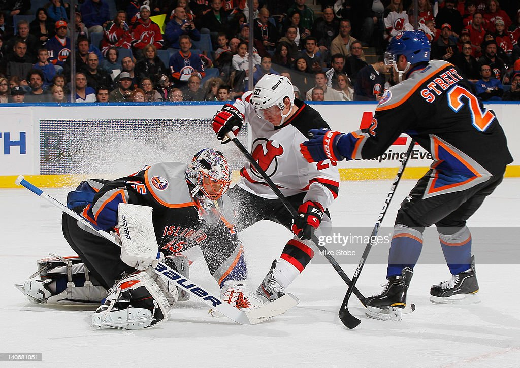 Goaltender Anders Nilsson #45 of the New York Islanders covers the puck as teammate <a gi-track='captionPersonalityLinkClicked' href=/galleries/search?phrase=Mark+Streit&family=editorial&specificpeople=636976 ng-click='$event.stopPropagation()'>Mark Streit</a> #2 reaches out for David Clarkson #23 of the New Jersey Devils at Nassau Veterans Memorial Coliseum on March 4, 2012 in Uniondale, New York.
