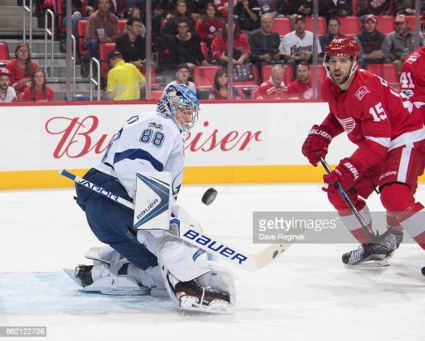 Goaltender Andrei Vasilevskiy of the Tampa Bay Lightning makes a save as Riley Sheahan of the Detroit Red Wings skates in for the rebound during an...