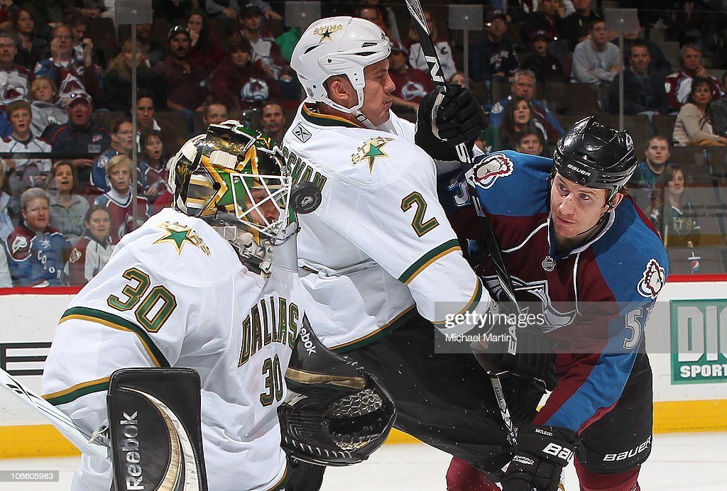 Goaltender Andrew Raycroft of the Dallas Stars blocks a shot on the face mask against Cody McLeod of the Colorado Avalanche as Nicklas Grossman of...