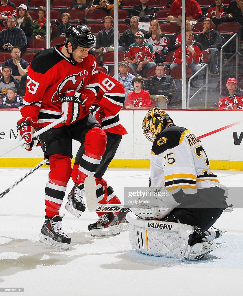 Goaltender <a gi-track='captionPersonalityLinkClicked' href=/galleries/search?phrase=Anton+Khudobin&family=editorial&specificpeople=722106 ng-click='$event.stopPropagation()'>Anton Khudobin</a> #35 of the Boston Bruins makes a save while being screened by David Clarkson #23 of the New Jersey Devils during the game at the Prudential Center on April 10, 2013 in Newark, New Jersey.