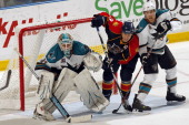 Goaltender Antti Niemi of the San Jose Sharks defends the net with the help of teammate Joe Pavelski against Stephen Weiss of the Florida Panthers at...