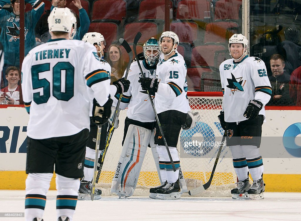 Goaltender Antti Niemi #31 of the San Jose Sharks is congratulated by teammates James Sheppared #15, Matt Irwin #52 as Chris Tierney #50 skates in following a 4-2 victory over the Arizona Coyotes at Gila River Arena on February 13, 2015 in Glendale, Arizona.