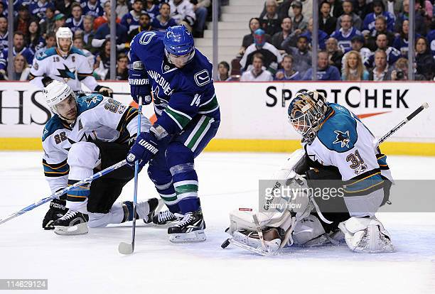 Goaltender Antti Niemi of the San Jose Sharks makes a save as Dan Boyle of the San Jose Sharks defends Alex Burrows of the Vancouver Canucks in the...