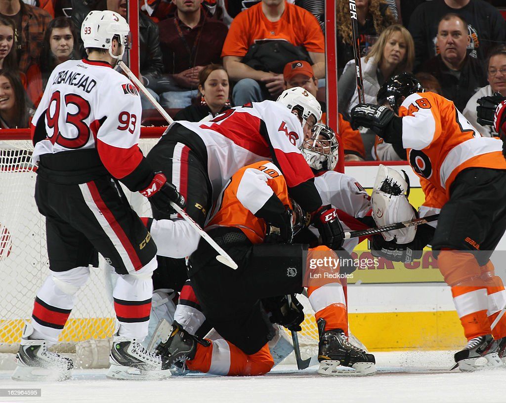 Goaltender Ben Bishop #30 of the Ottawa Senators is in the middle of a scrum with teammates Mike Zibanejad #93, Patrick Wiercioch #46, and Brayden Schenn #10 and Danny Briere #48 of the Philadelphia Flyers on March 2, 2013 at the Wells Fargo Center in Philadelphia, Pennsylvania.
