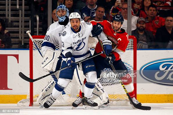 Goaltender Ben Bishop of the Tampa Bay Lightning defends the net with the help of teammate JT Brown against Derek MacKenzie of the Florida Panthers...