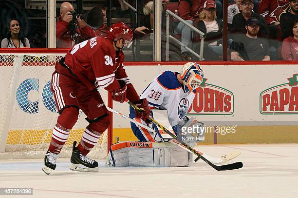 Goaltender Ben Scrivens of the Edmonton Oilers makes a save on a shot as Rob Klinkhammer of the Arizona Coyotes looks for a rebound during the third...