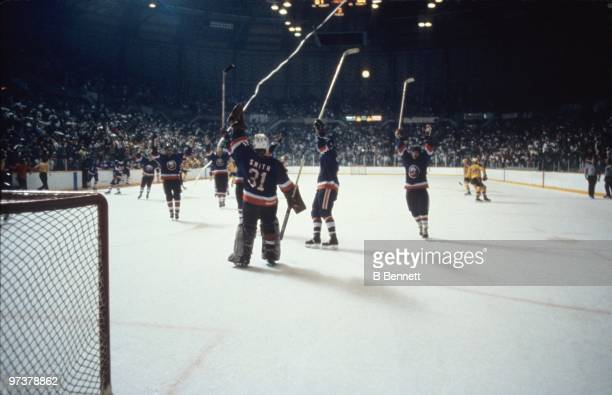 Goaltender Billy Smith of the New York Islanders raises his glove to celebrate after winning the 1982 Stanley Cup Finals against the Vancouver...