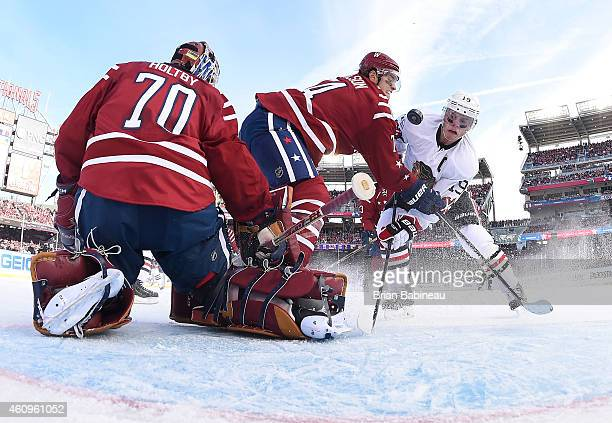Goaltender Braden Holtby and John Carlson of the Washington Capitals defend the play of Jonathan Toews of the Chicago Blackhawks to the net in the...