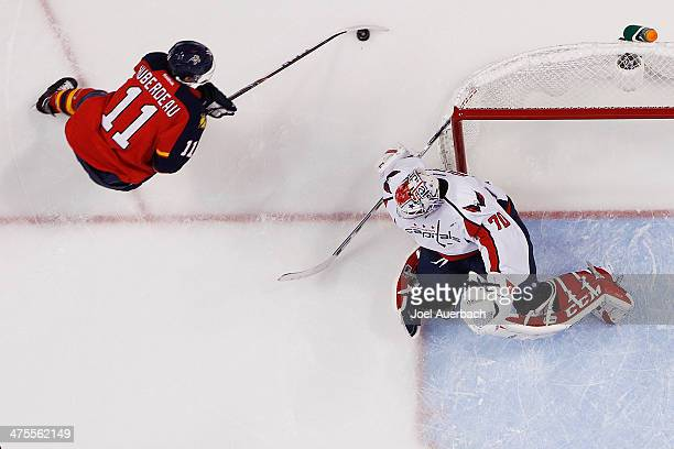 Goaltender Braden Holtby of the Washington Capital guards the post as Jonathan Huberdeau of the Florida Panthers circles the net with the puck at the...