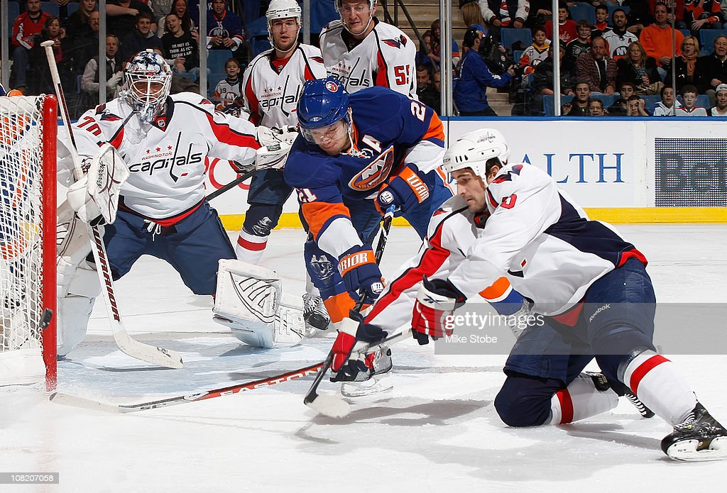 Goaltender Braden Holtby of the Washington Capitals and teammate Tom Poti defend the net as Kyle Okposo of the New York Islanders looks for the...