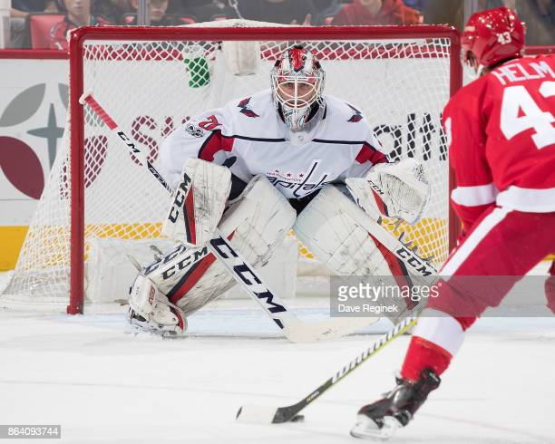 Goaltender Braden Holtby of the Washington Capitals follows the puck as Darren Helm of the Detroit Red Wings skates in during an NHL game at Little...