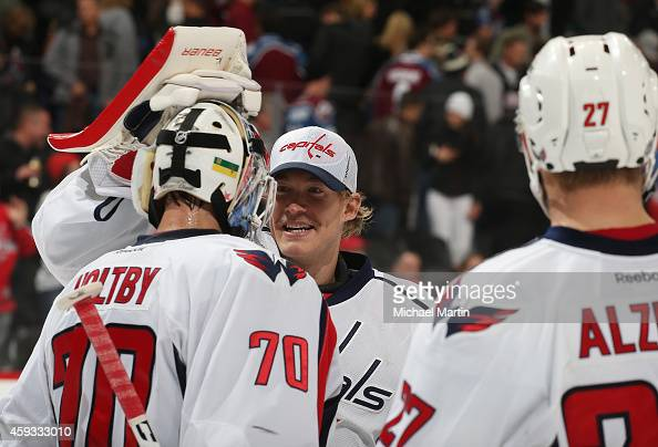 Goaltender Braden Holtby of the Washington Capitals is congratulated by teammate Justin Peters after winning against the Colorado Avalanche at the...