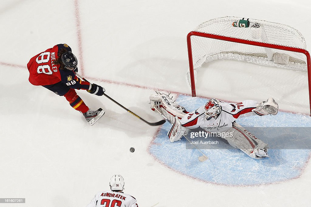 Goaltender <a gi-track='captionPersonalityLinkClicked' href=/galleries/search?phrase=Braden+Holtby&family=editorial&specificpeople=5370964 ng-click='$event.stopPropagation()'>Braden Holtby</a> #70 of the Washington Capitals stops a shot by Peter Mueller #88 of the Florida Panthers during second period action at the BB&T Center on February 12, 2013 in Sunrise, Florida. The Capitals defeated the Panthers 6-5 in overtime.
