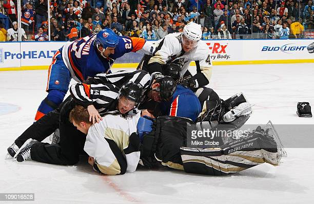 Goaltender Brent Johnson of the Pittsburgh Penguins gets tangled up with Milan Jurcina and Michael Haley of the New York Islanders on February 11...