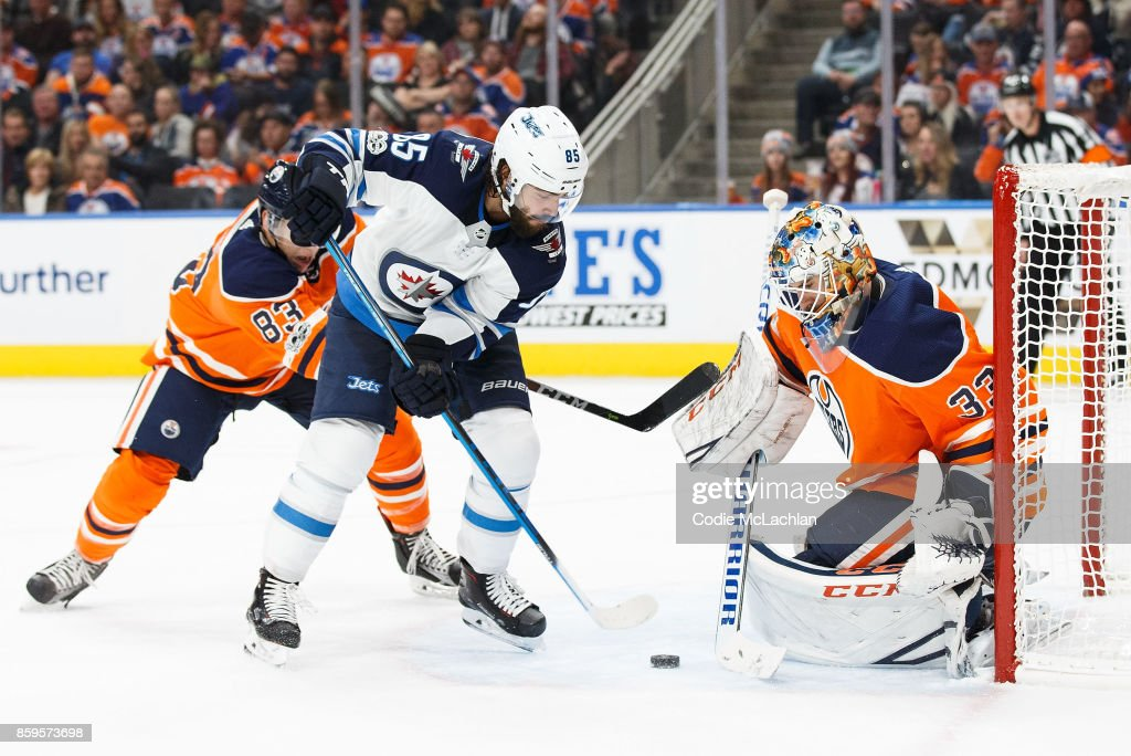 Goaltender Cam Talbot #33 of the Edmonton Oilers makes a save against Mathieu Perreault #85 of the Winnipeg Jets at Rogers Place on October 9, 2017 in Edmonton, Canada.