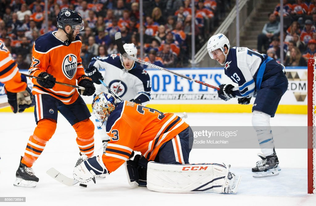 Goaltender Cam Talbot #33 of the Edmonton Oilers makes a save as Brandon Tanev #13 of the Winnipeg Jets waits in the crease at Rogers Place on October 9, 2017 in Edmonton, Canada.