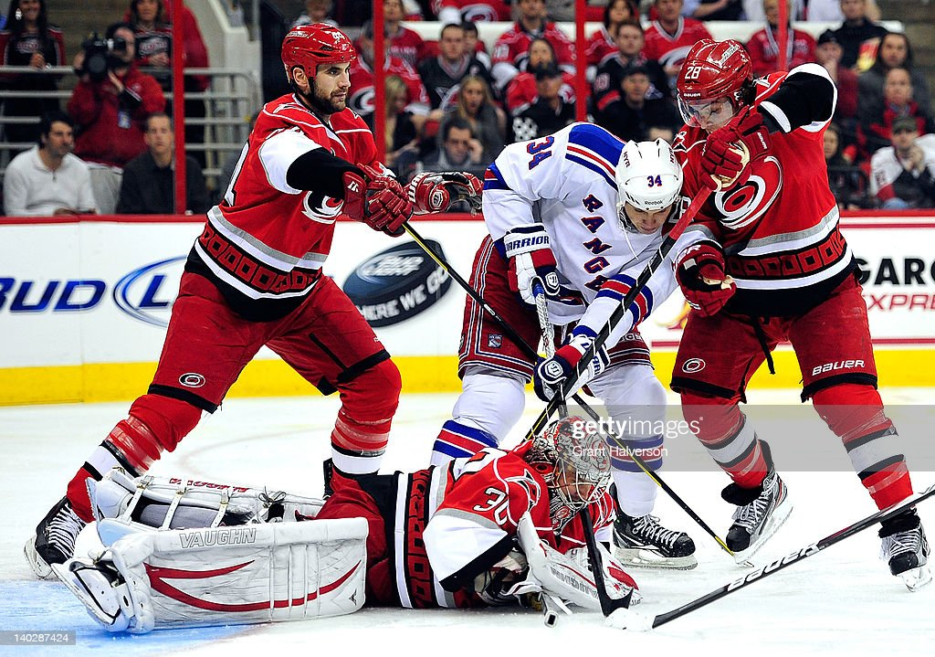 Goaltender <a gi-track='captionPersonalityLinkClicked' href=/galleries/search?phrase=Cam+Ward&family=editorial&specificpeople=453216 ng-click='$event.stopPropagation()'>Cam Ward</a> #30 dives on a loose puck as Jay HArrison #44 and Justin Faulk #28 of the Carolina Hurricanes defend John Mitchell #34 of the New York Rangers during play at the RBC Center on March 1, 2012 in Raleigh, North Carolina.