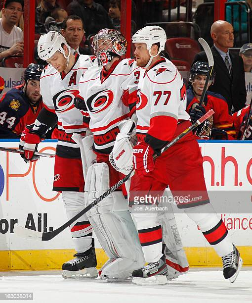 Goaltender Cam Ward is helped off the ice by Joe Corvo and Tim Gleason of the Carolina Hurricanes after being injured in second period action against...