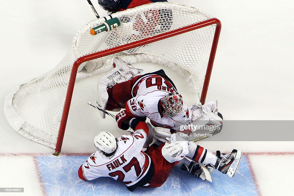 Goaltender <a gi-track='captionPersonalityLinkClicked' href=/galleries/search?phrase=Cam+Ward&family=editorial&specificpeople=453216 ng-click='$event.stopPropagation()'>Cam Ward</a> #30 of the Carolina Hurricanes collides with teammate Justin Faulk #27 and Jack Skille of the Florida Panthers (not pictured) at the BB&T Center on March 3, 2013 in Sunrise, Florida. Ward left the game after an injury from this play.