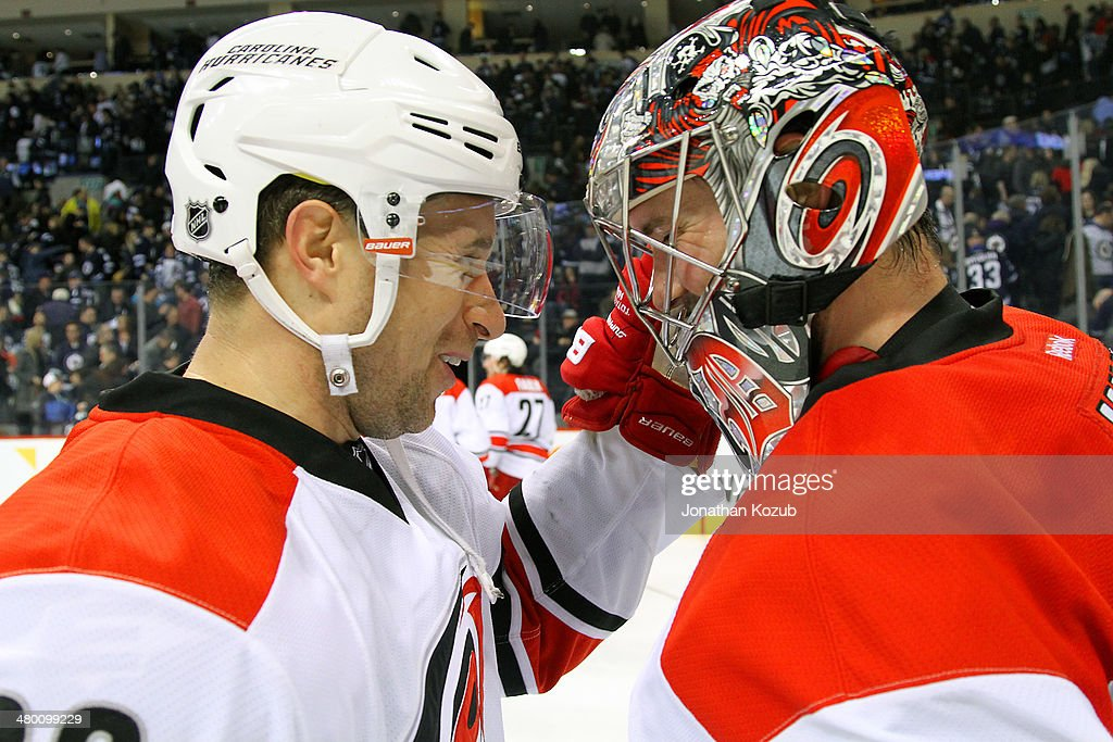 Goaltender <a gi-track='captionPersonalityLinkClicked' href=/galleries/search?phrase=Cam+Ward&family=editorial&specificpeople=453216 ng-click='$event.stopPropagation()'>Cam Ward</a> #30 of the Carolina Hurricanes gets congratulated by teammate <a gi-track='captionPersonalityLinkClicked' href=/galleries/search?phrase=John-Michael+Liles&family=editorial&specificpeople=206866 ng-click='$event.stopPropagation()'>John-Michael Liles</a> #26 after backstopping the Canes to a 3-2 victory over the Winnipeg Jets at the MTS Centre on March 22, 2014 in Winnipeg, Manitoba, Canada.