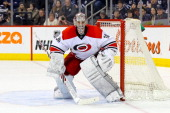 Goaltender Cam Ward of the Carolina Hurricanes keeps an eye on the play as he guards the net during third period action against the Winnipeg Jets at...