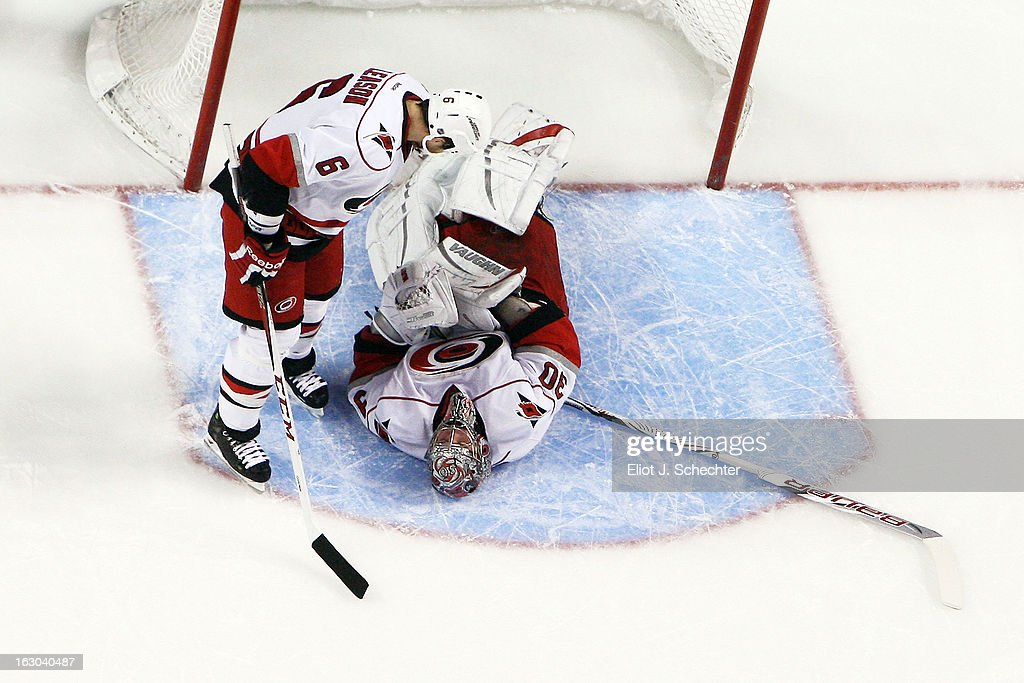 Goaltender <a gi-track='captionPersonalityLinkClicked' href=/galleries/search?phrase=Cam+Ward&family=editorial&specificpeople=453216 ng-click='$event.stopPropagation()'>Cam Ward</a> #30 of the Carolina Hurricanes lies on his back in pain while teammate <a gi-track='captionPersonalityLinkClicked' href=/galleries/search?phrase=Tim+Gleason&family=editorial&specificpeople=211575 ng-click='$event.stopPropagation()'>Tim Gleason</a> #6 comes over to check on him against the Florida Panthers at the BB&T Center on March 3, 2013 in Sunrise, Florida.