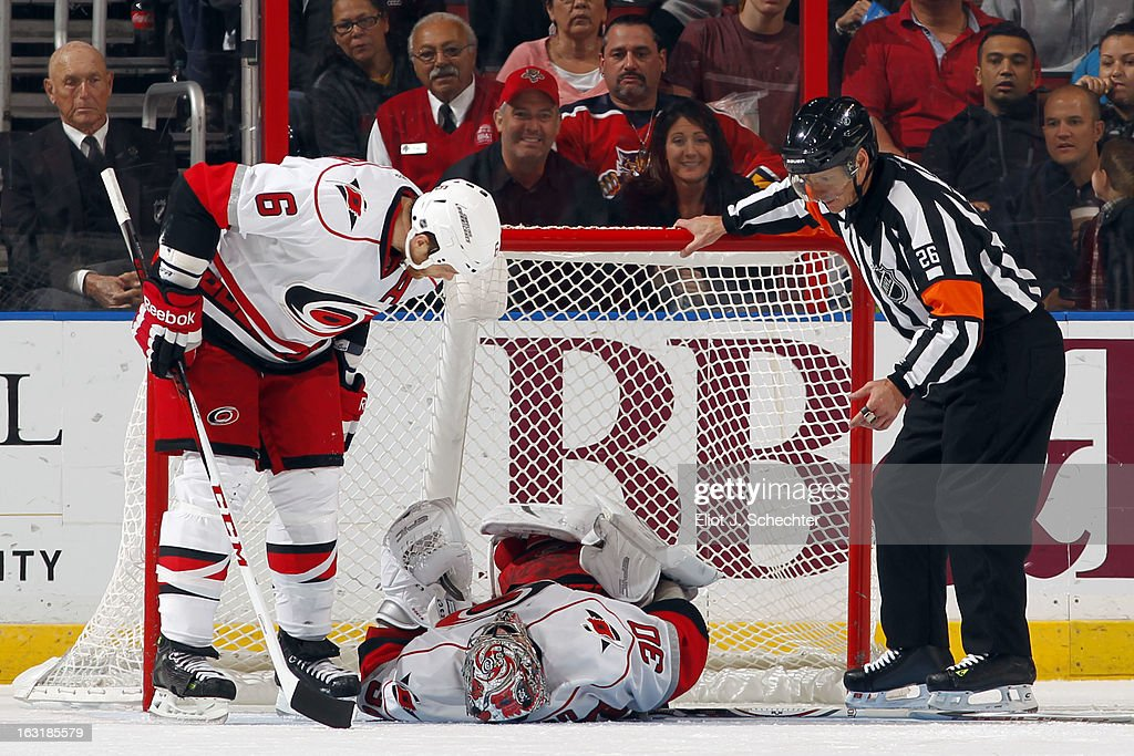 Goaltender Cam Ward #30 of the Carolina Hurricanes lies on his back in pain while teammate Tim Gleason #6 comes over to check on him against the Florida Panthers at the BB&T Center on March 3, 2013 in Sunrise, Florida.